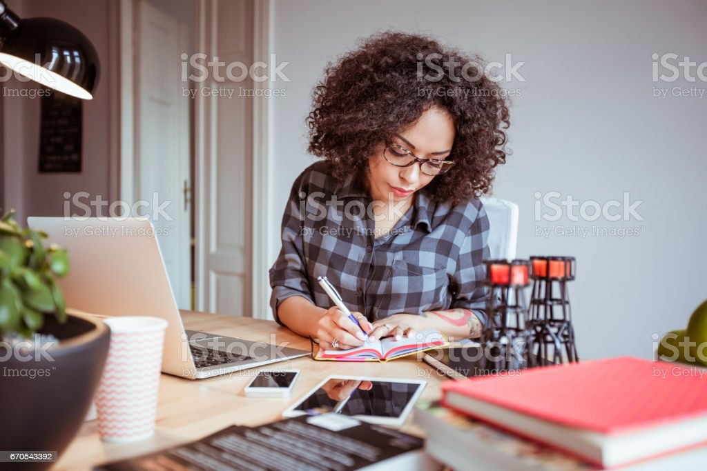 Afro american woman in a home office taking notes stock photo