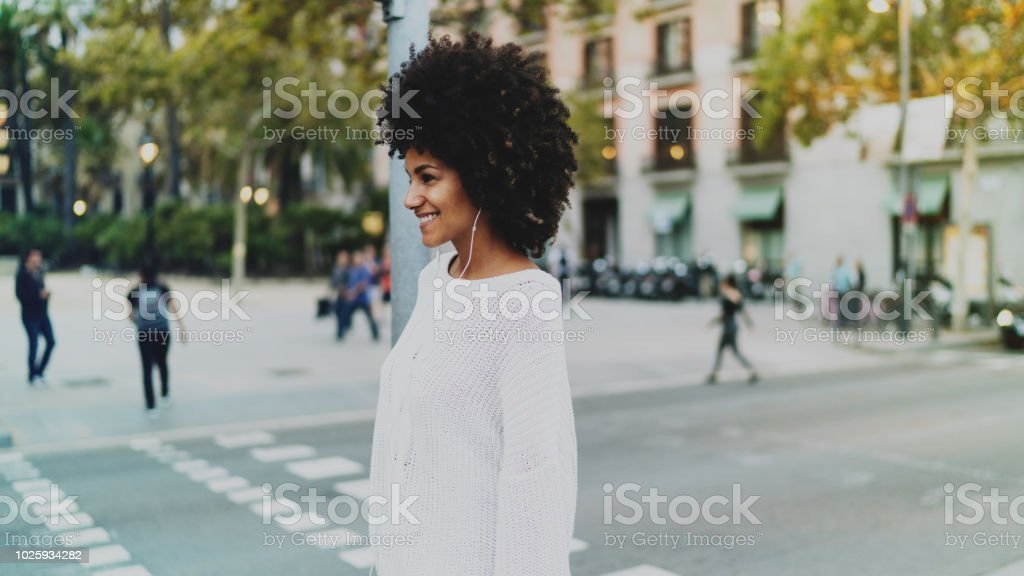Afro american woman listening to radio online in headphones while...