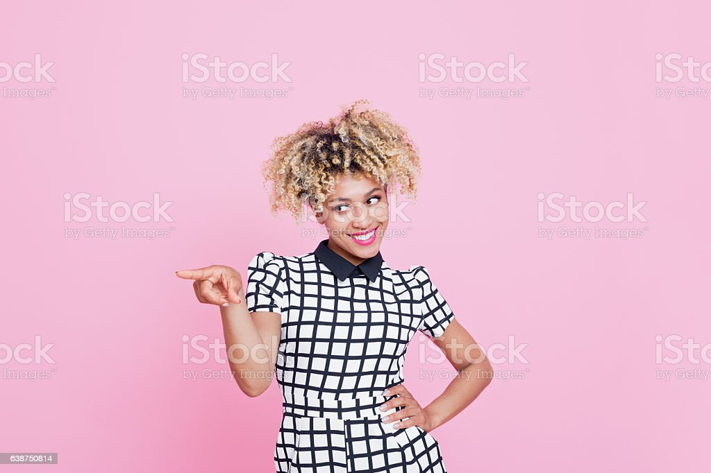 Afro American Woman Pointing At Empty Copy Space Portrait of happy young woman pointing with index finger to copy space and looking away. Studio shot, pink background 20-24 Years Stock Photo