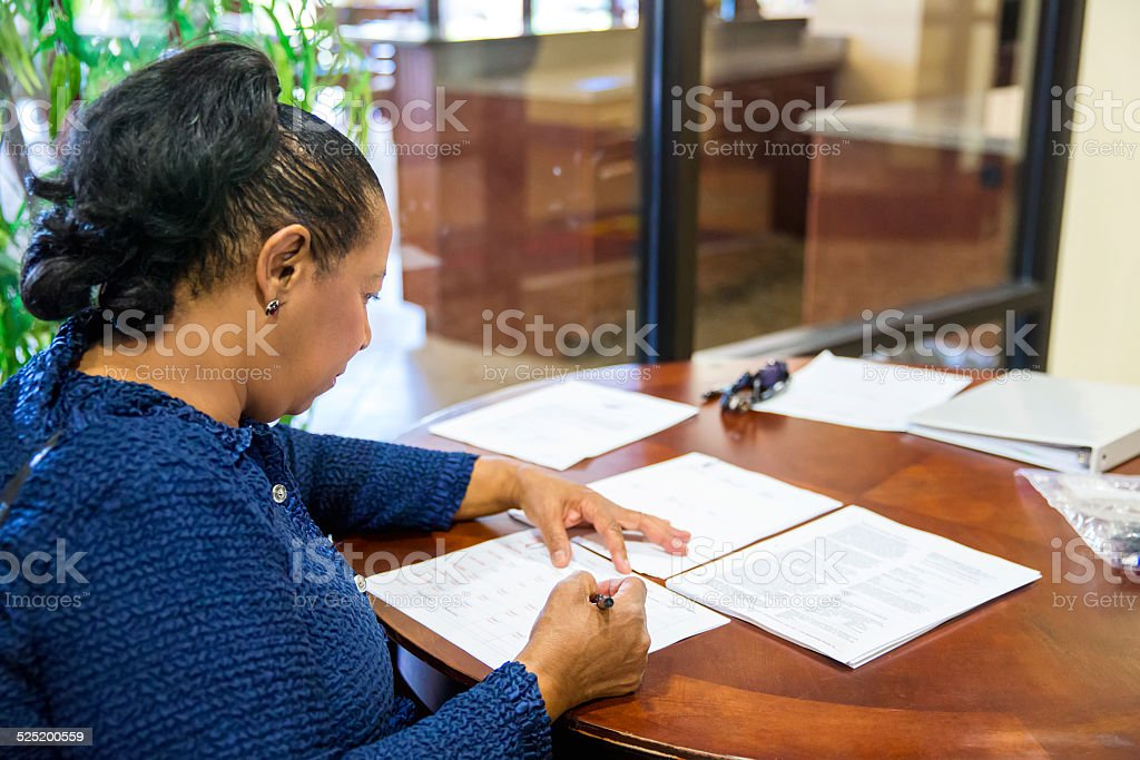 Afro American woman sitting at a table filling job application stock photo