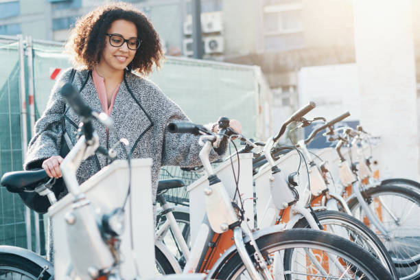 Afro american woman taking a bicycle in a bike sharing platform stock photo