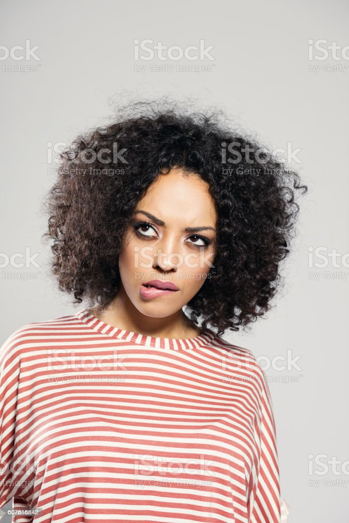 Afro american woman taking a decision Portrait of pensive afro american young woman wearing striped top, standing against grey background, looking up. Adult Stock Photo
