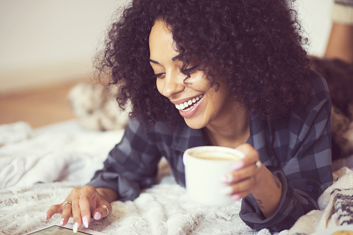 Afro American Woman Using A Digital Tablet At Home Stock Photo - Download Image Now