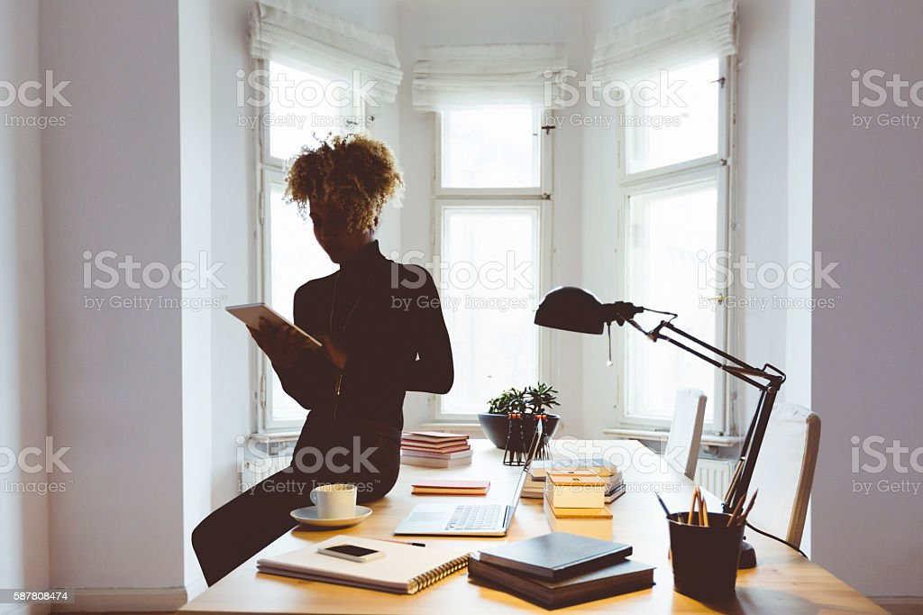 Afro american woman using a digital tablet in an office Afro american young woman using a digital tablet in a home office. Adult Stock Photo