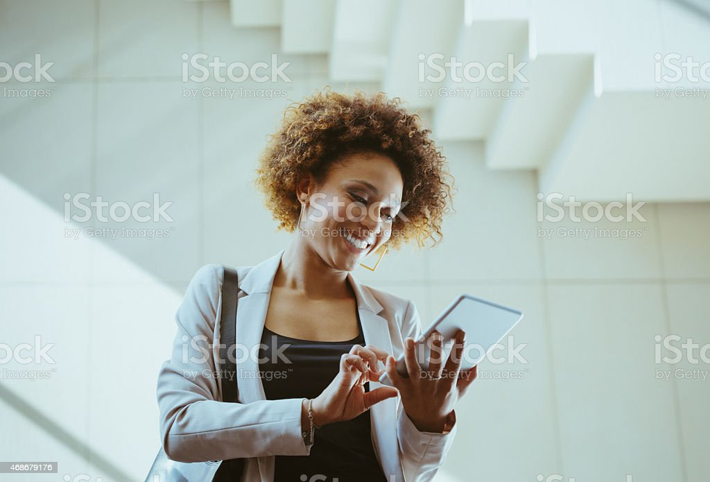 Afro american woman using a digital tablet Happy afro american businesswoman wearing jacket standing against white wall and stairs in an office and using a digital tablet. 2015 Stock Photo