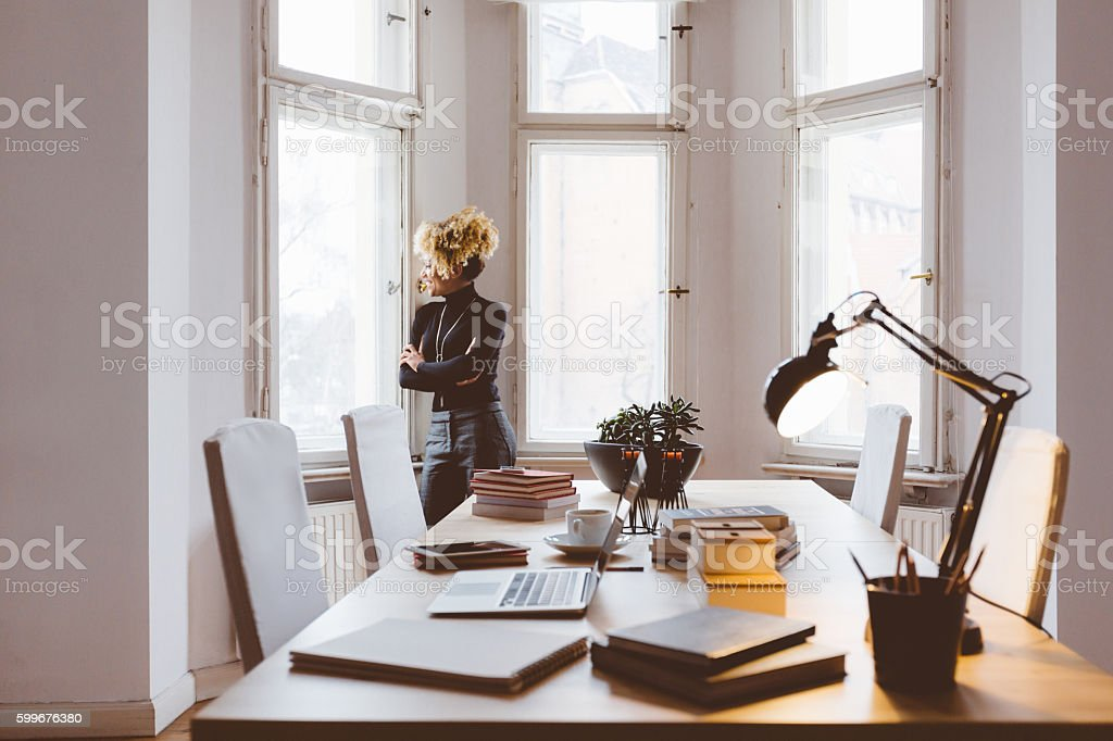 Afro american woman using in a home office Afro american young woman in a home office, stading by the window. Adult Stock Photo