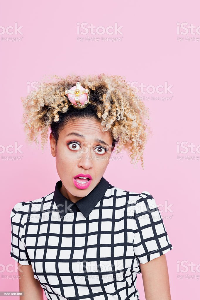 Afro American woman with diva attitude with little crown headbands Portrait of unhappy  afro american young woman with diva attitude. She is wearing grid check playsuit, and little crown headband. Standing against pink background looking into the camera. 25-29 Years Stock Photo