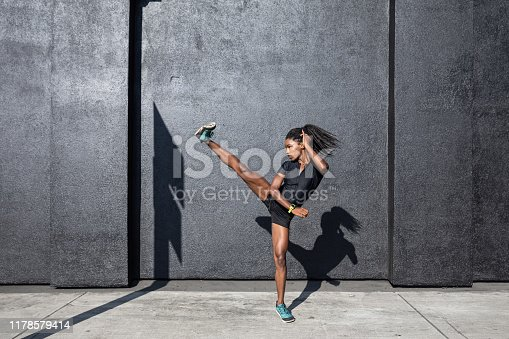 Afro american woman with dreadlocks in a great athletic shape working out and training hard outdoors