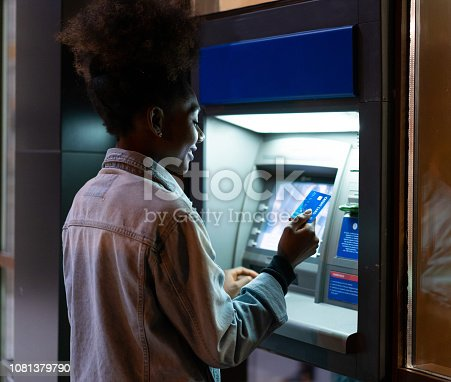 Afro American woman withdrawing money at the ATM