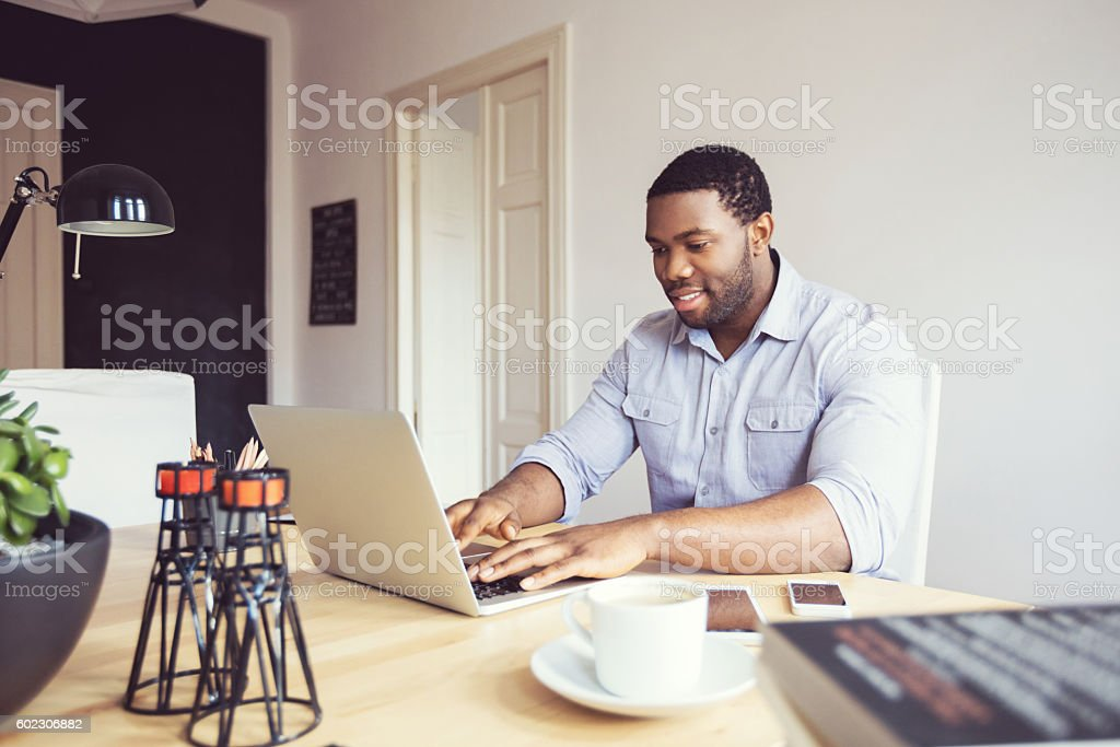 Afro american young businessman typing on laptop in an office Happy afro american young man wearing shirt using laptop at home or in the office.  Adult Stock Photo