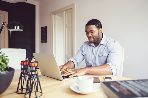 Afro American Young Businessman Typing On Laptop In An Office Stock Photo - Download Image Now