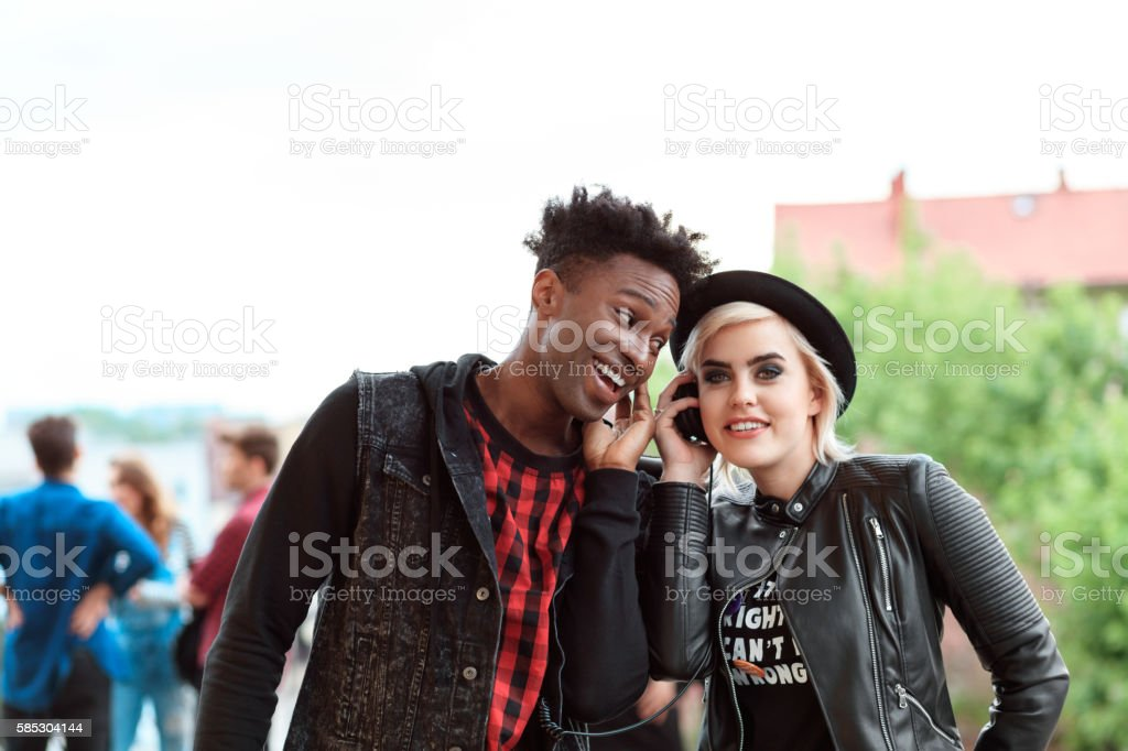 Afro american young guy and blonde girl using mobiles outdoor Afro american young guy and blonde girl using smart phones outdoor. Group of people in the background. 20-29 Years Stock Photo