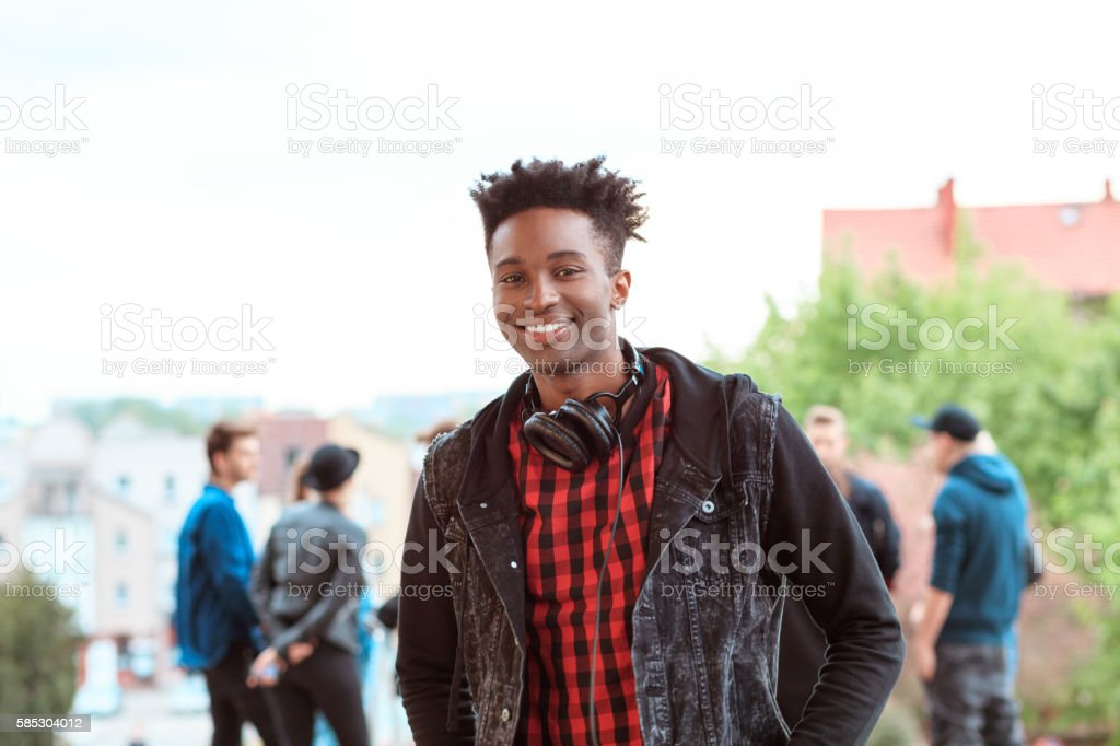 Afro american young guy smiling outdoor Outdoor portrait of afro american young guy smiling at camera. Group of people in the background. 20-29 Years Stock Photo