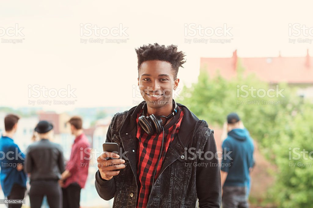 Afro american young guy smiling outdoor Outdoor portrait of afro american young guy smiling at camera, holding smart phone in hand. Group of people in the background. 20-29 Years Stock Photo