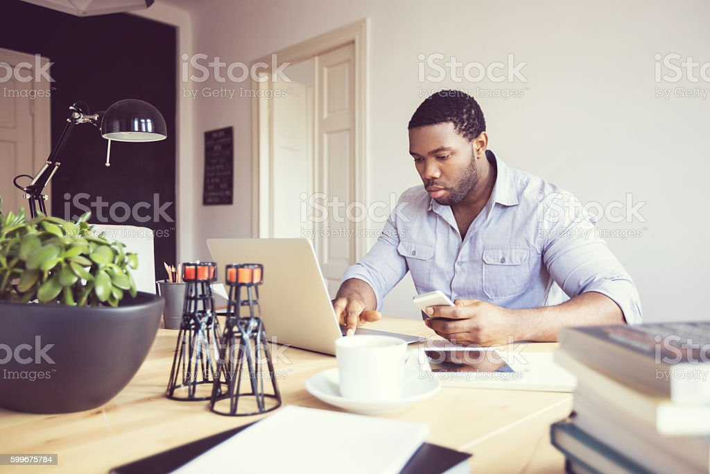 Afro american young man in a home office Afro american young man sitting at the desk in a home office, using laptop and smart phone. Adult Stock Photo