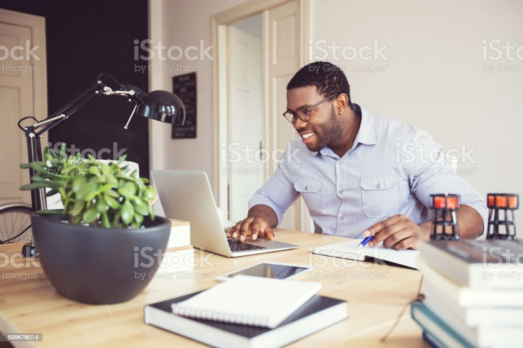 Afro american young man in a home office - foto de acervo
