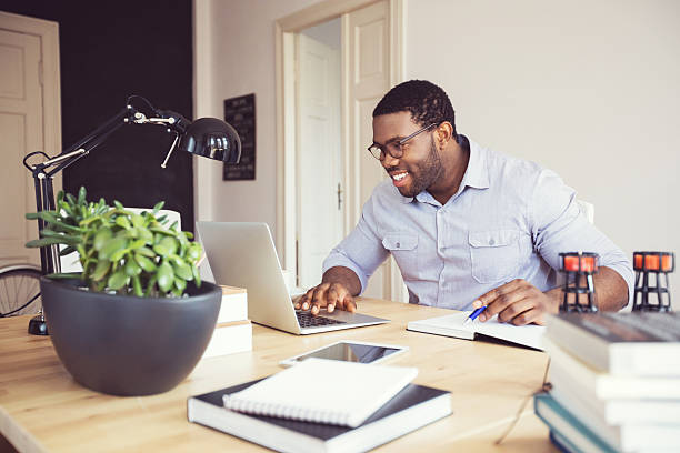 afro american young man in a home office - trabalhando de casa - fotografias e filmes do acervo