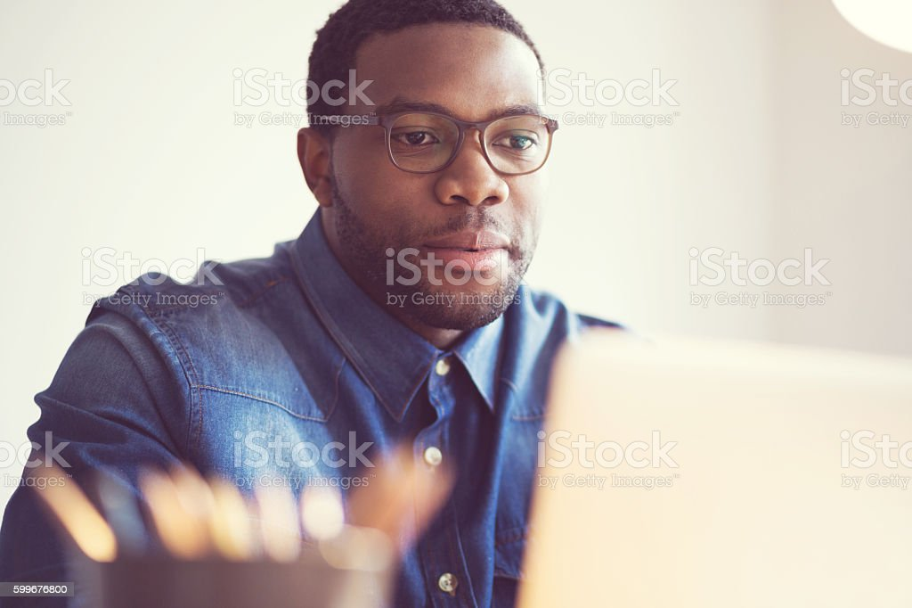 Afro american young man in a home office Afro american young man using laptop at home or in the office. Adult Stock Photo