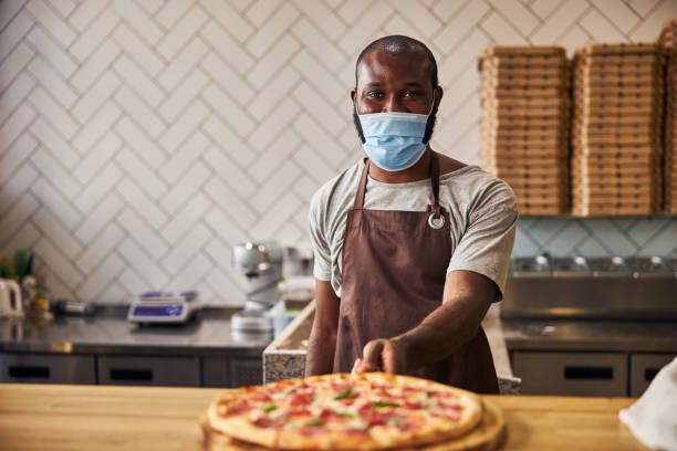 Afro American young man in medical mask holding pepperoni pizza stock photo