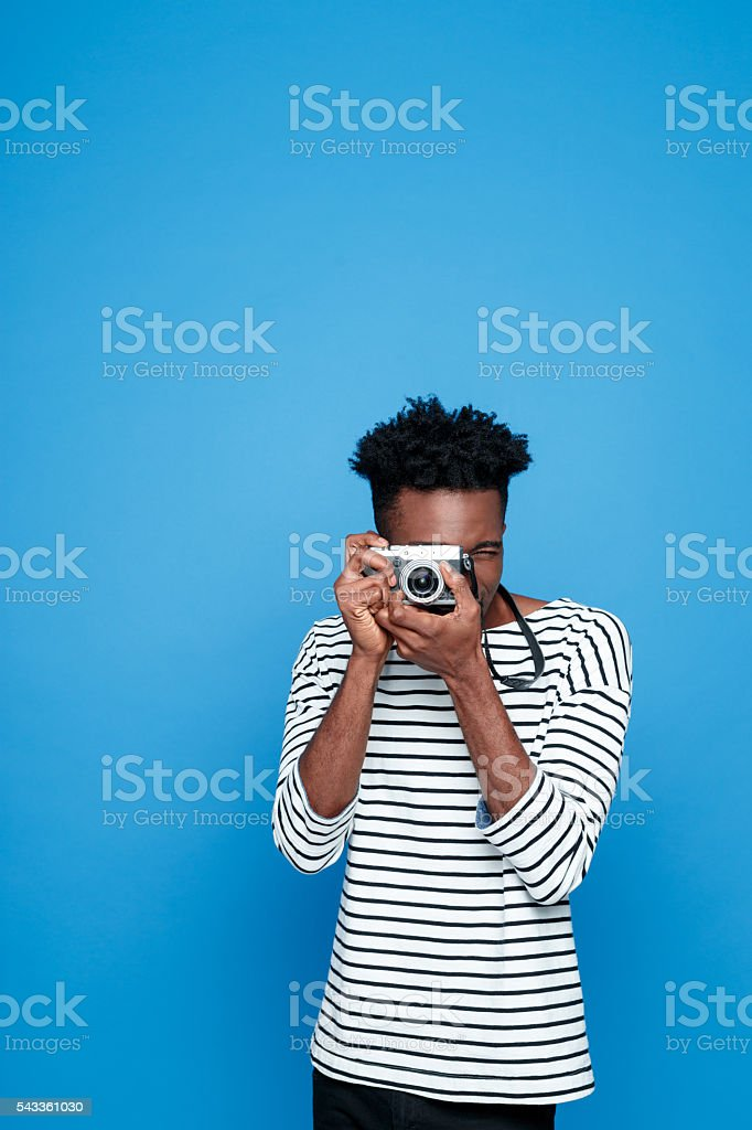 Afro american young man photographing Portrait of afro american guy wearing striped long sleeved t-shirt, using a camera. Studio shot, blue background.  Adult Stock Photo