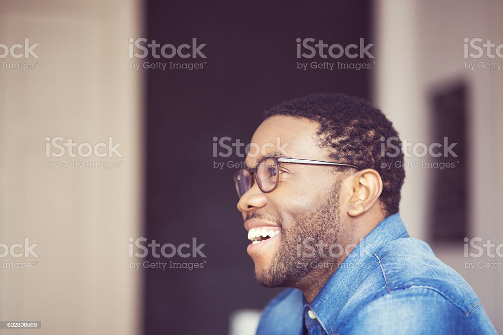 Afro american young man smiling, side view Afro american young man wearing denim shirt and glasses, smiling. Side view. Indoor shot. Adult Stock Photo