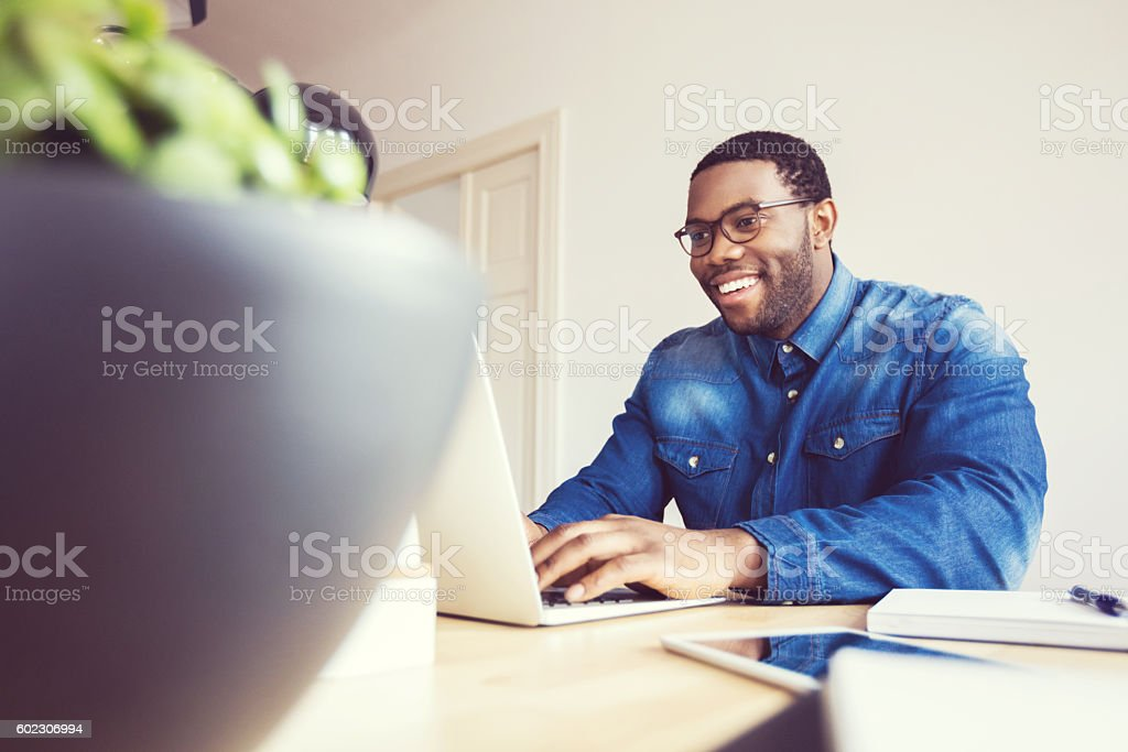 Afro american young man typing on laptop in an office Happy afro american young man wearing denim shirt using laptop at home or in the office.  Adult Stock Photo