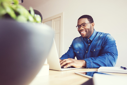 Afro American Young Man Typing On Laptop In An Office Stock Photo - Download Image Now