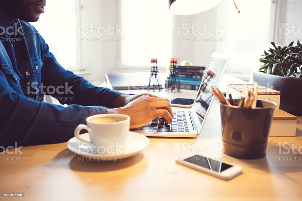 Afro american young man typing on laptop in an office Afro american young man using laptop at home or in the office. Close up of hands. Adult Stock Photo