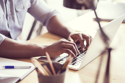 Afro American Young Man Typing On Laptop Stock Photo - Download Image Now