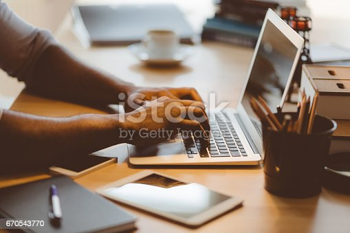 Close up shot of afro american man typing on laptop at his work desk in office
