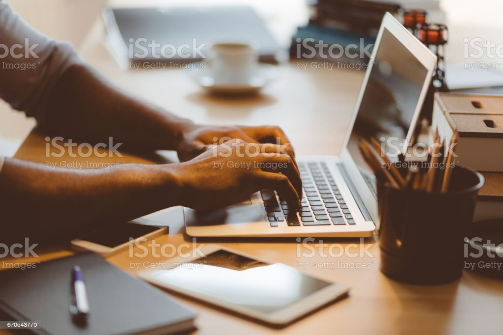 Afro american young man typing on laptop stock photo