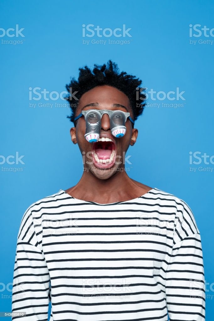 Afro american young man wearing funny eyes mask Portrait of fearful afro american guy wearing striped long sleeved t-shirt and funny eyes glasses, staring at the camera. Studio shot, blue background.  Adult Stock Photo