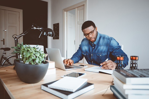 Shot of afro american young man in a home office using laptop and taking notes. Black guy sitting at table and working from home office.