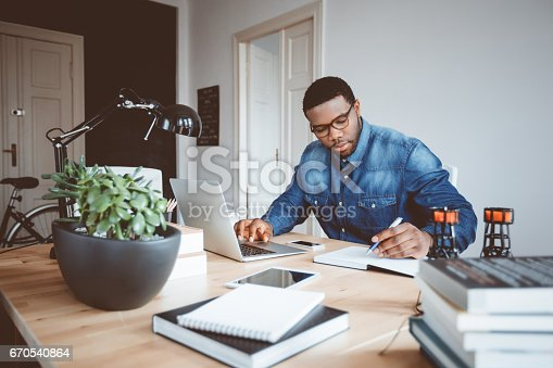 istock Afro american young man working at home office 670540864