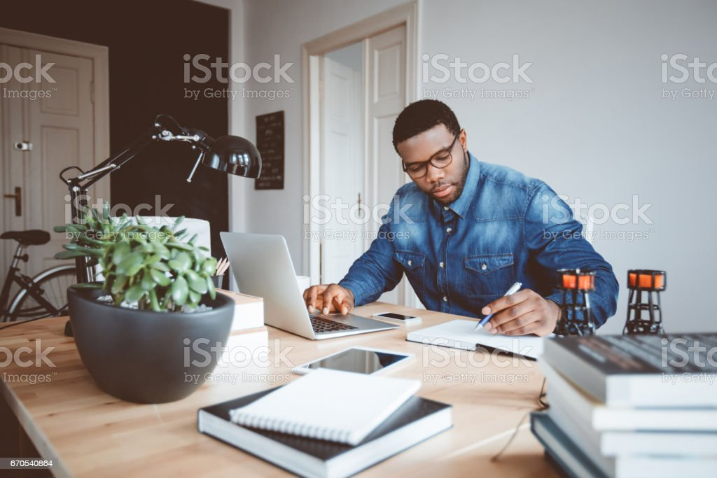 Afro american young man working at home office stock photo