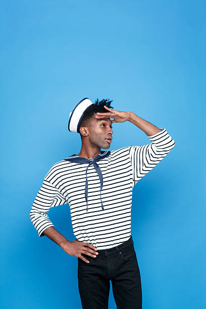 Afro american young sailor looking away Portrait of afro american young man in sailor style outfit, looking away withe raised hand. Studio portrait, blue background. sailor suit stock pictures, royalty-free photos & images