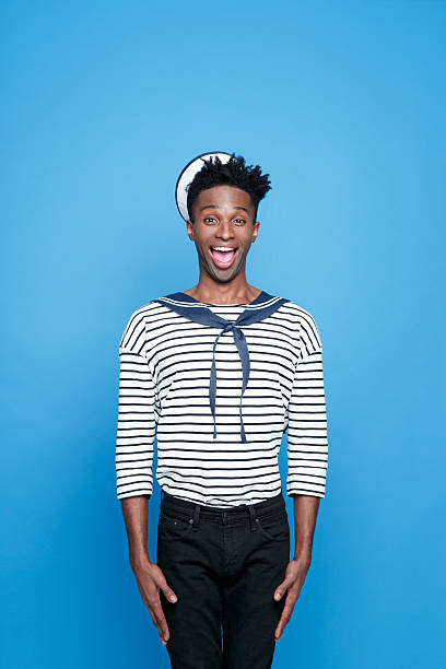 Afro american young sailor standing at attention Portrait of happy afro american young man in sailor style outfit, standing at atrention, looking at camera. Studio portrait, blue background. sailor suit stock pictures, royalty-free photos & images