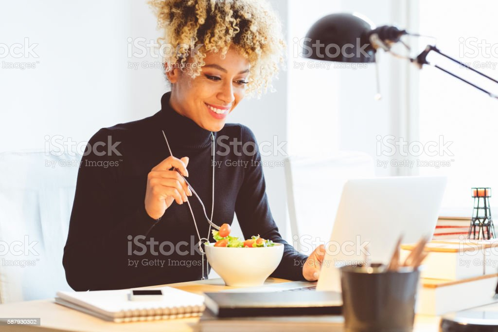 Afro american young woman eating lunch at the desk Beautiful afro american young woman sitting at the desk in an office and eating lunch, using laptop at the same time. Adult Stock Photo