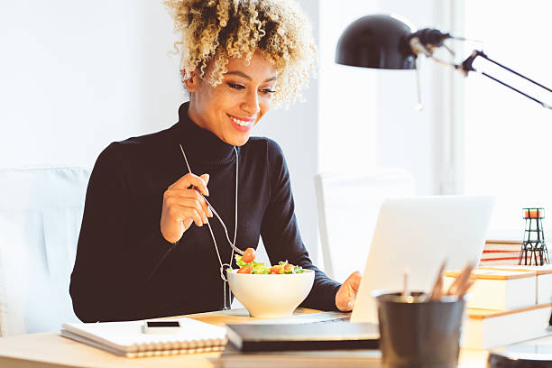 afro american young woman eating lunch at the desk - öğle yemeği stok fotoğraflar ve resimler
