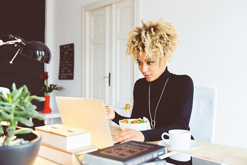 Afro American Young Woman Eating Lunch At The Desk Stock Photo - Download Image Now