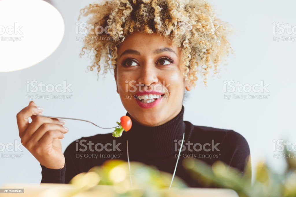 Afro american young woman eating salad Beautiful afro american young woman eating salad, holding a fort with tomato in hand and smiling. Close up of face. Adult Stock Photo
