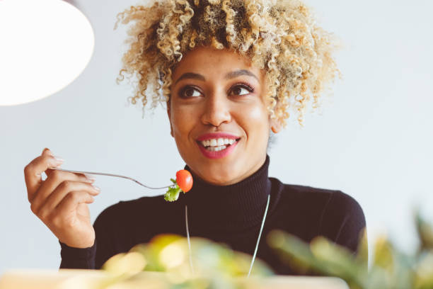 Afro american young woman eating salad - Photo