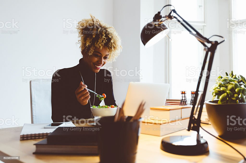 Afro american young woman eating salat at the desk Beautiful afro american young woman sitting at the desk in an office and eating lunch, using laptop at the same time, laughing. Adult Stock Photo