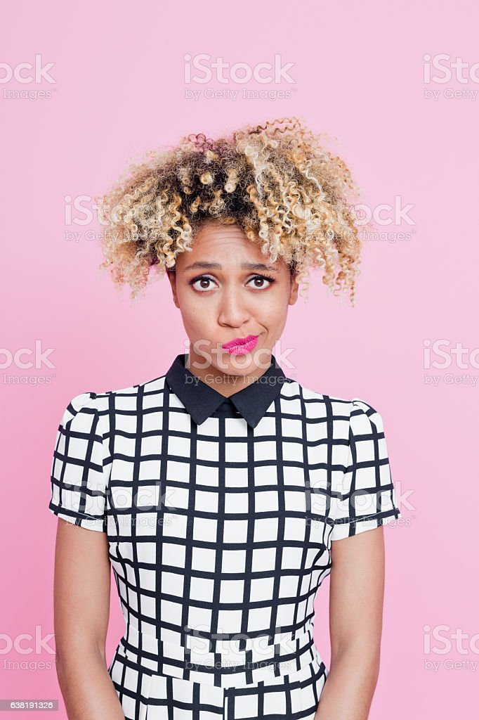 Afro American young woman having a doubts Portrait of beautiful afro american young woman having a doubts about something. She is wearing grid check playsuit, standing against pink background. 25-29 Years Stock Photo