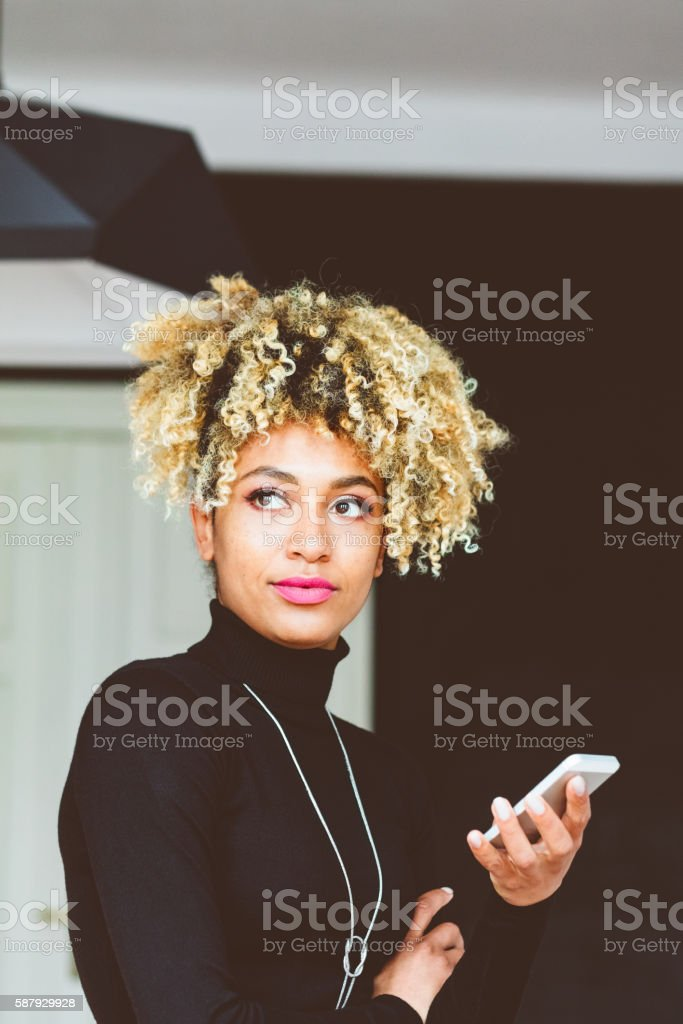 Afro american young woman holding a smart phone Beautiful afro american young woman holding a smart phone in hand indoors. Adult Stock Photo