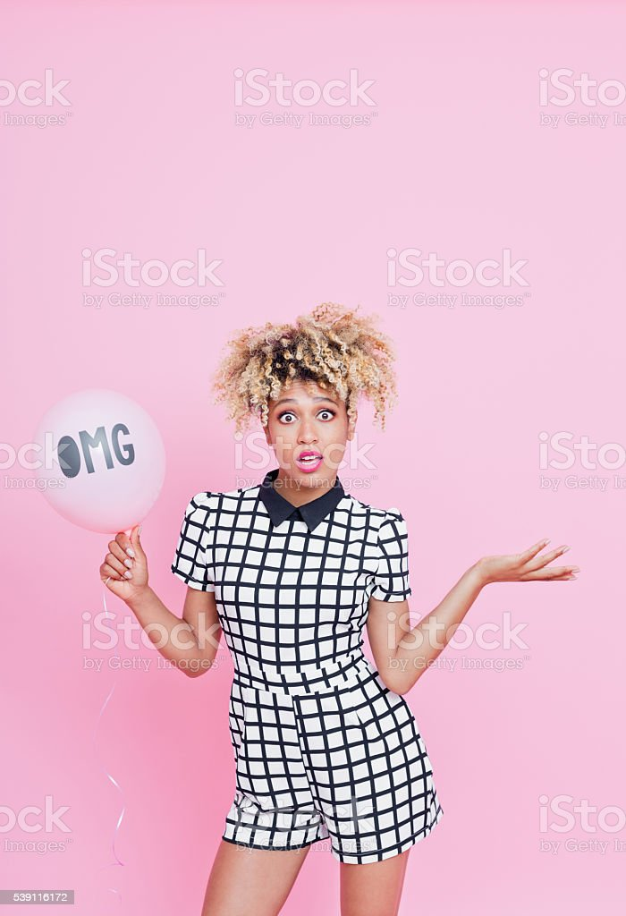 Afro American young woman holding balloon with OMG sign Portrait of beautiful afro american young woman with surprised expression on her face. She is wearing grid check playsuit, standing against pink background and holding OMG pink balloon. 25-29 Years Stock Photo