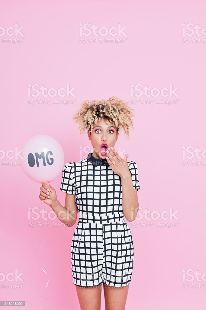 Afro American young woman holding balloon with OMG sign Summer portrait of beautiful afro american young woman with surprised expression on her face. She is wearing grid check playsuit, standing against pink background and holidng OMG pink balloon. 25-29 Years Stock Photo