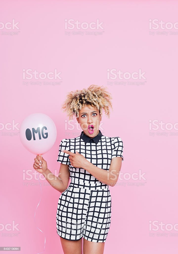 Afro American young woman holding balloon with OMG sign Summer portrait of beautiful afro american young woman with surprised expression on her face. She is wearing grid check playsuit, standing against pink background and pointing at OMG pink balloon. 2016 Stock Photo