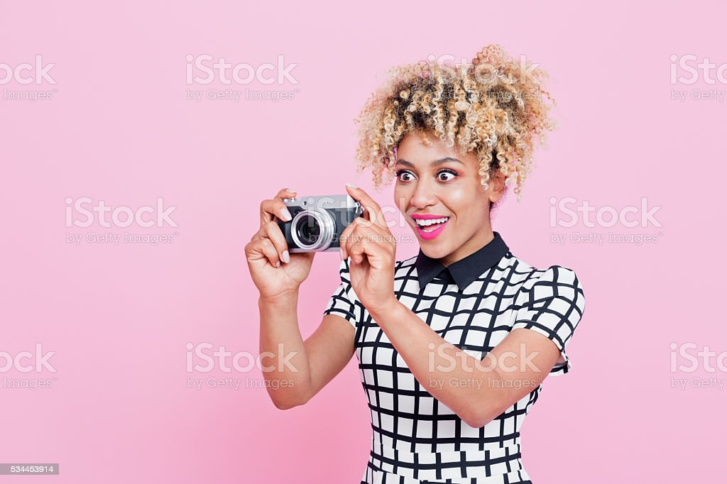 Afro American young woman holding camera Summer portrait of beautiful afro american young woman with surprised expression on her face. Wearing grid check playsuit, standing against pink background and holding camera. Studio shot, one person, pink background. 25-29 Years Stock Photo