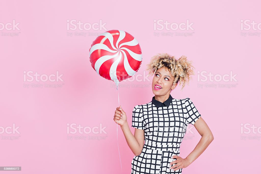 Afro American young woman holding candy balloon Summer portrait of happy, energetic afro american young woman wearing grid check playsuit, standing against pink background, holding candy balloon with funny expression. 2016 Stock Photo